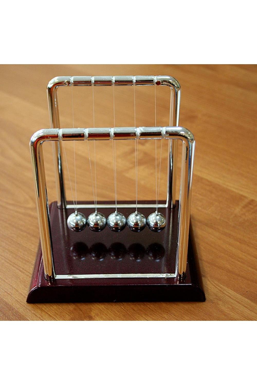Украшение для интерьера Шары Ньютона средниеИнтерьер<br>Небольшая настольная кинетическая скульптура в собранном виде демонстрирует закон сохранения энергии, открытый Исааком Ньютоном. Достаточно отвести и отпустить один из крайних шариков, и Вы увидите, как это работает. Завораживающее медитативное постукивание блестящих шаров на Вашем столе поможет сосредоточиться при обдумывании или наоборот, расслабиться после тяжелой работы. Комплектность: подставка -1шт., стойка с леской и шарами -1шт. Размеры в собранном виде: 13.5х14,5х11.5<br>