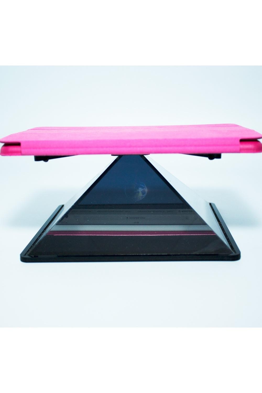 Пирамида для iPad 3D реальностьРазвлечения и вечеринки<br>Голографическая пирамида для планшета – это конструкция, превращающая планшет в проектор трехмерного изображения. Она состоит из четырех специальных зеркал, которые ставятся сверху на устройство и отражают картинку, делая ее объемной. Размер пирамиды небольшой: она легко помещается в рюкзак. С помощью такого приспособления и айпада вы создадите настоящую голограмму. Посмотрите на летающую внутри бабочку, колибри или плывущую медузу, переливающуюся разными цветами. Насладитесь красотой и необычностью изображения и поделитесь этим с друзьями, удивив их новой пирамидой. Пирамида умеет превращать двухмерные картинки в трехмерные изображения, которые выглядят, как настоящие, с какой стороны ни посмотреть. Для этого нужно запустить видео или открыть фото на планшете, а сверху него установить мини-проектор. На этом сайте есть много видео для пирамиды. Размер: 22х22х13см. Материал: Пластик<br>